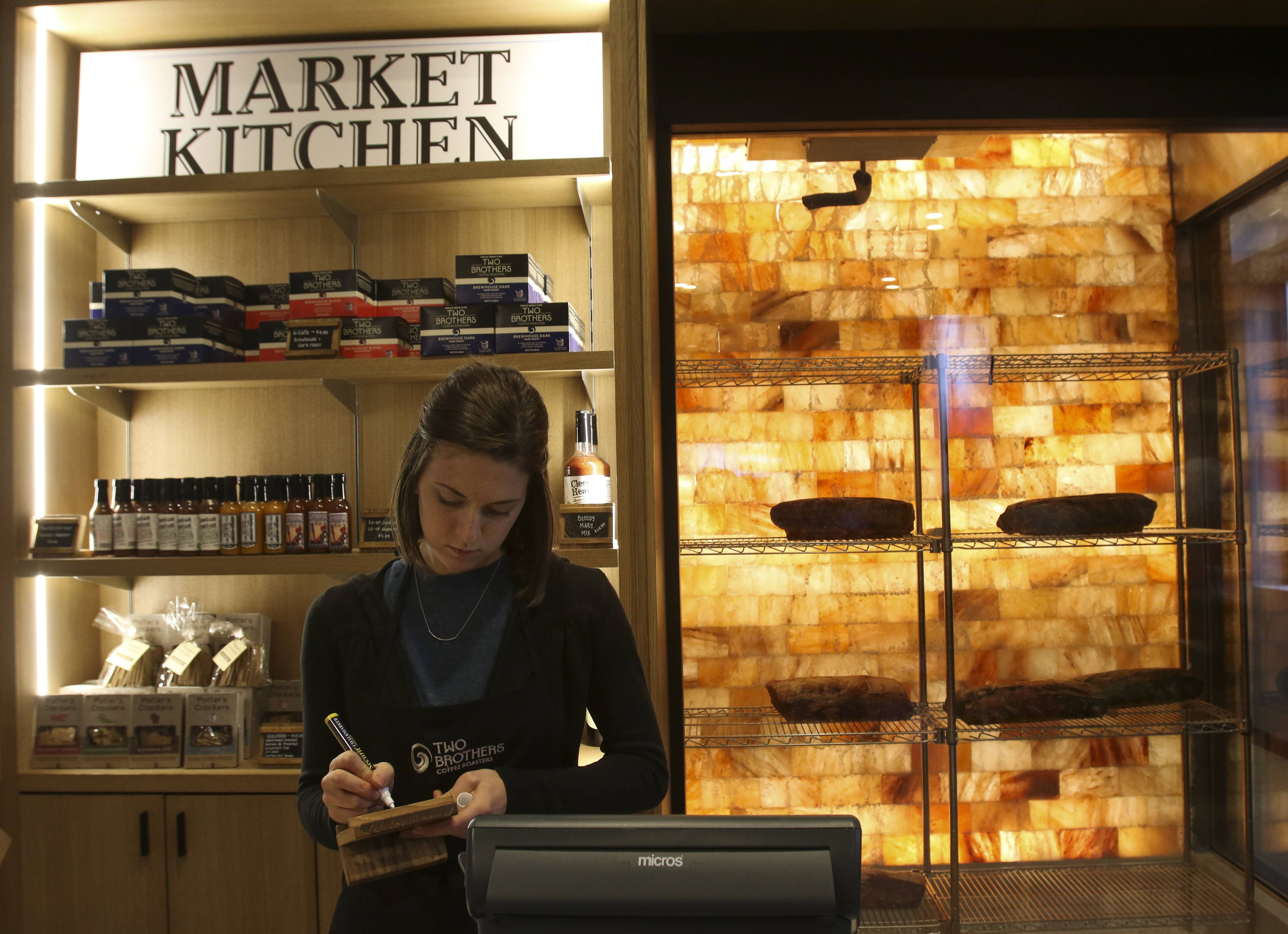 Barista Alie Walters takes notes in the cafe on the first floor of The Craftsman by Two Brothers in downtown Naperville, where a Himalayan salt drying room on the right cures meats in-house. The three-story restaurant hosted its grand opening last weekend.