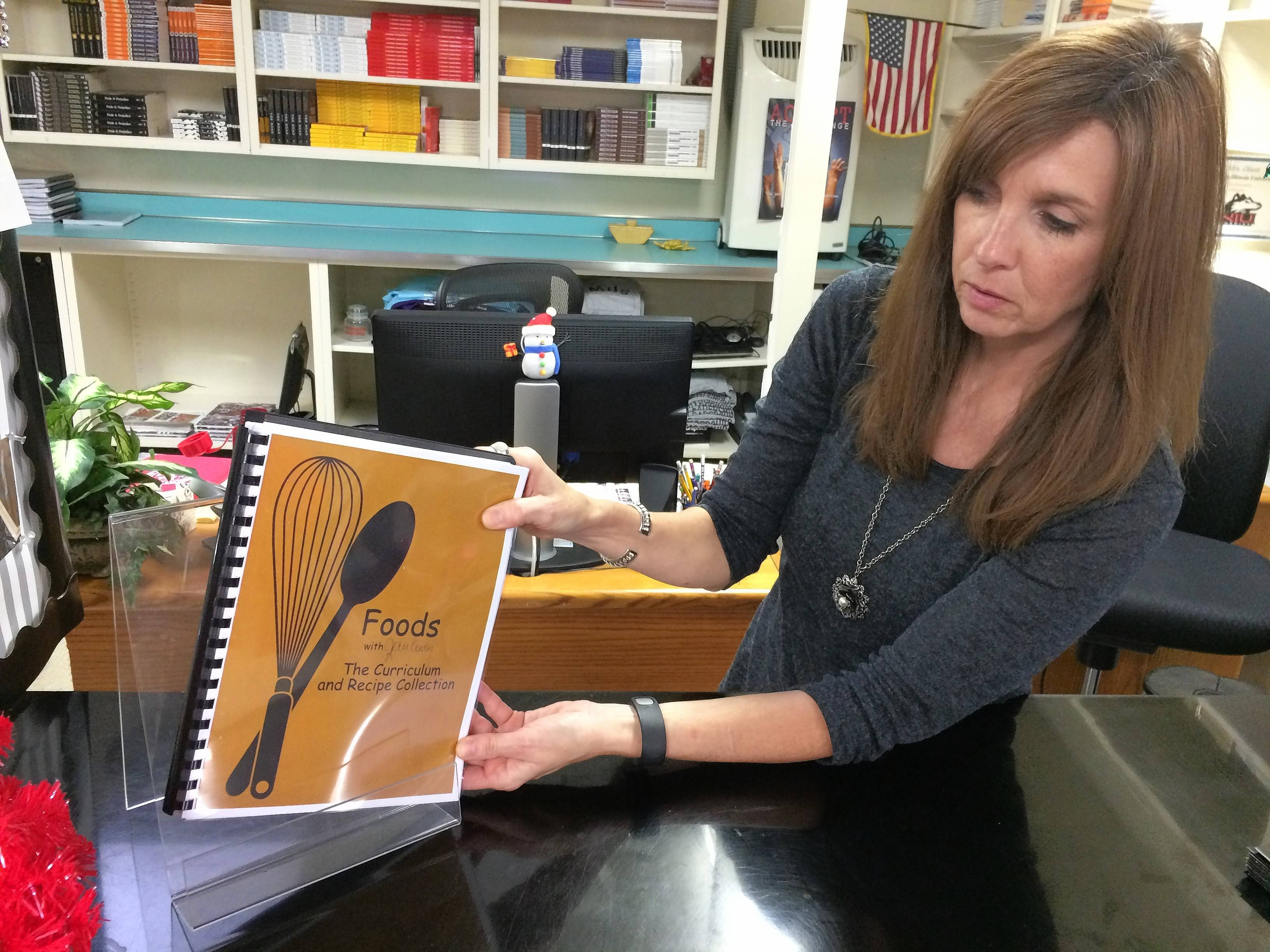 Mundelein High School bookstore clerk KC Olson adjusts a display copy of the cookbook honoring longtime teacher Jerri Craven, who died in September.
