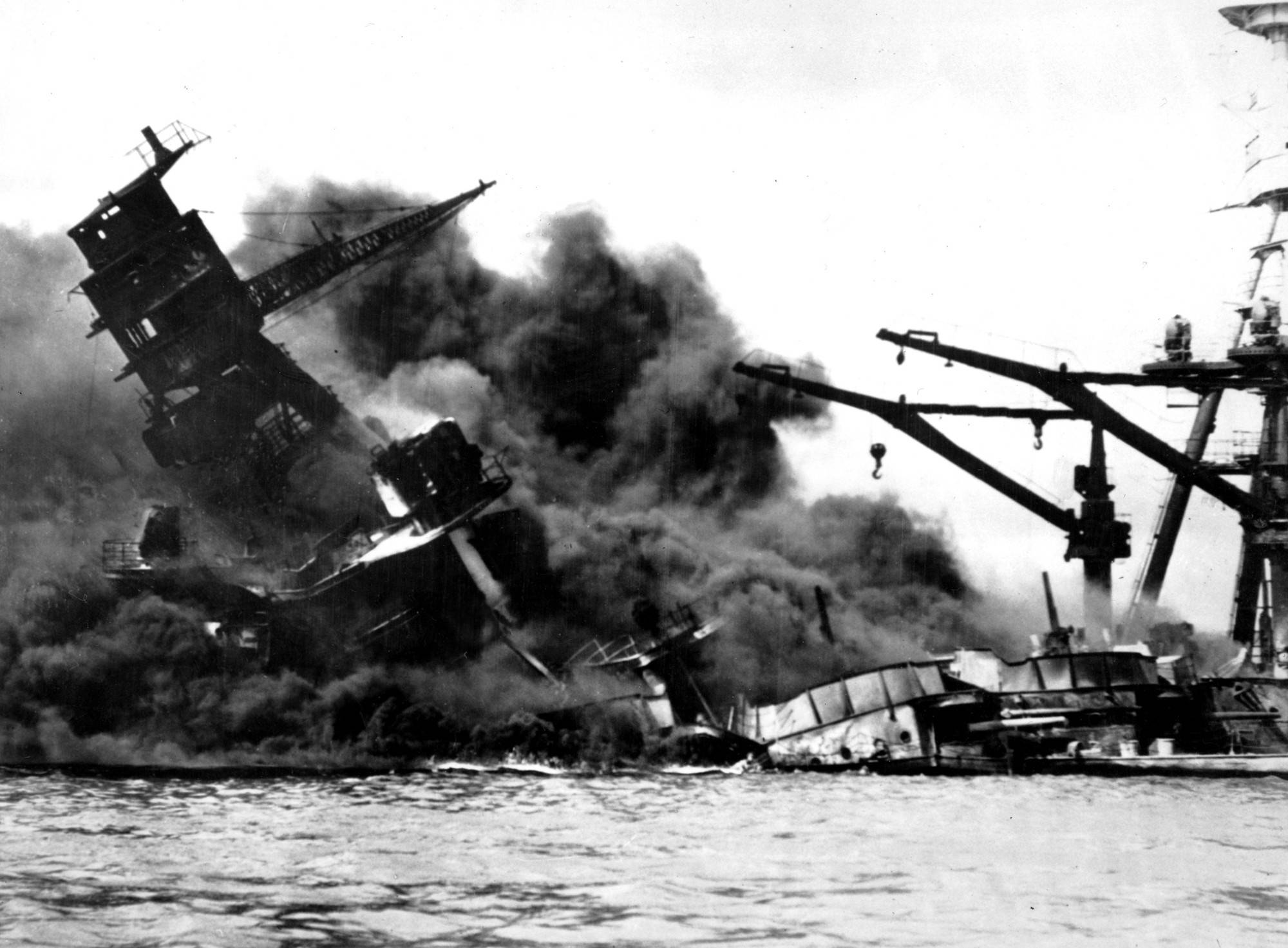 The battleship USS Arizona belches smoke as it topples over into the sea during a Japanese surprise attack on Pearl Harbor, Hawaii, in this Dec. 7, 1941 file photo. (AP Photo/FILE)