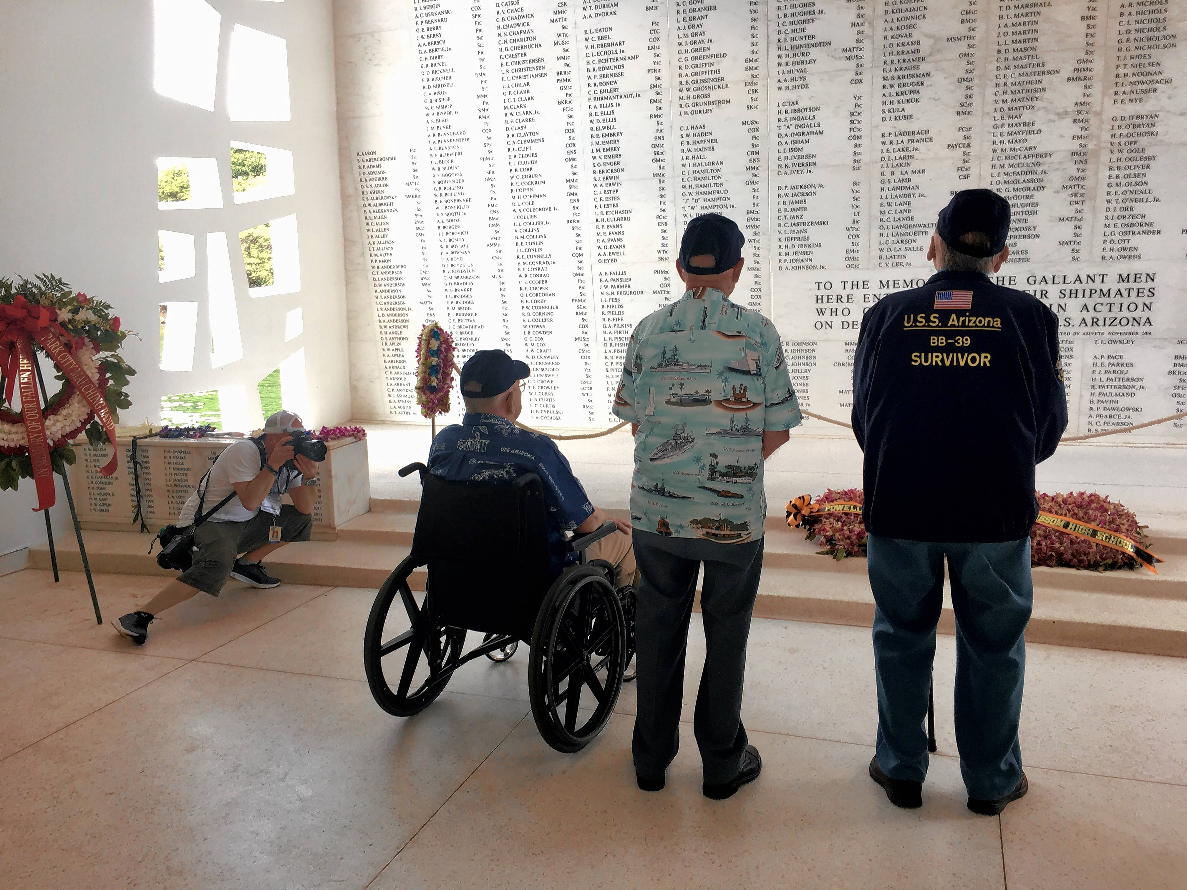 Controlling his emotions, photographer Paolo Cascio of Schaumburg captures three veterans who survived the Dec. 7, 1941, attack that sank their ship as the trio pay tribute to those who went down with the USS Arizona.