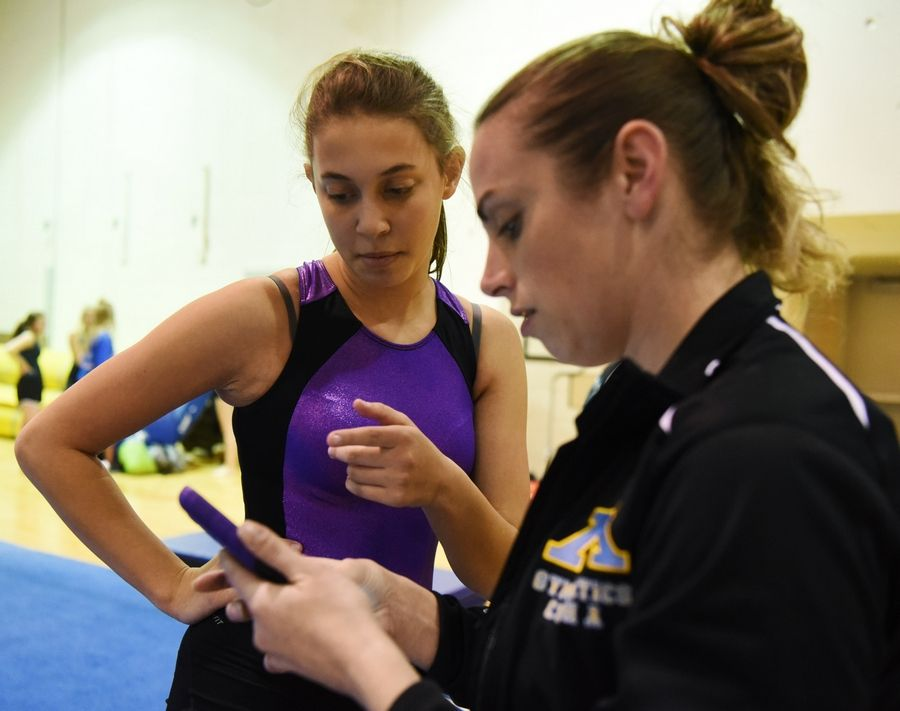 Maine West High School sophomore gymnast Rayna Davis, left, views video of herself practicing her floor exercise routine with coach Amanda Harrison.