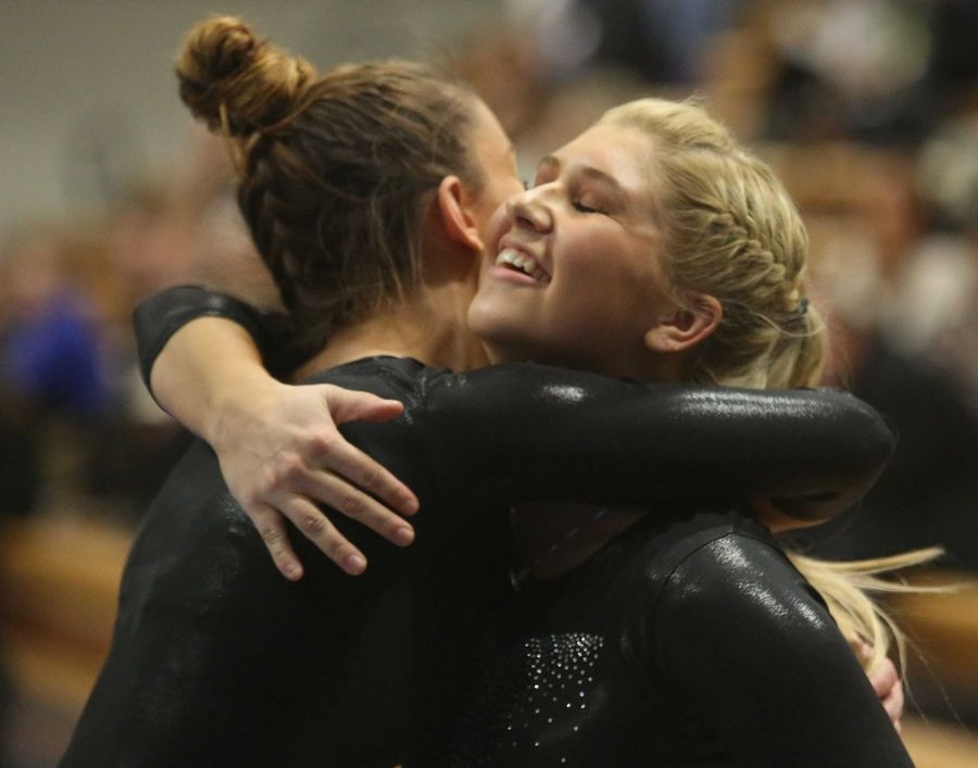 U-46 co-op's Emma Pawelkiewicz, left, is congratulated by teammate Nykia Wetterman after a beam routine during varsity gymnastics action at Mack Olson Gym on the campus of Geneva High School Wednesday night.