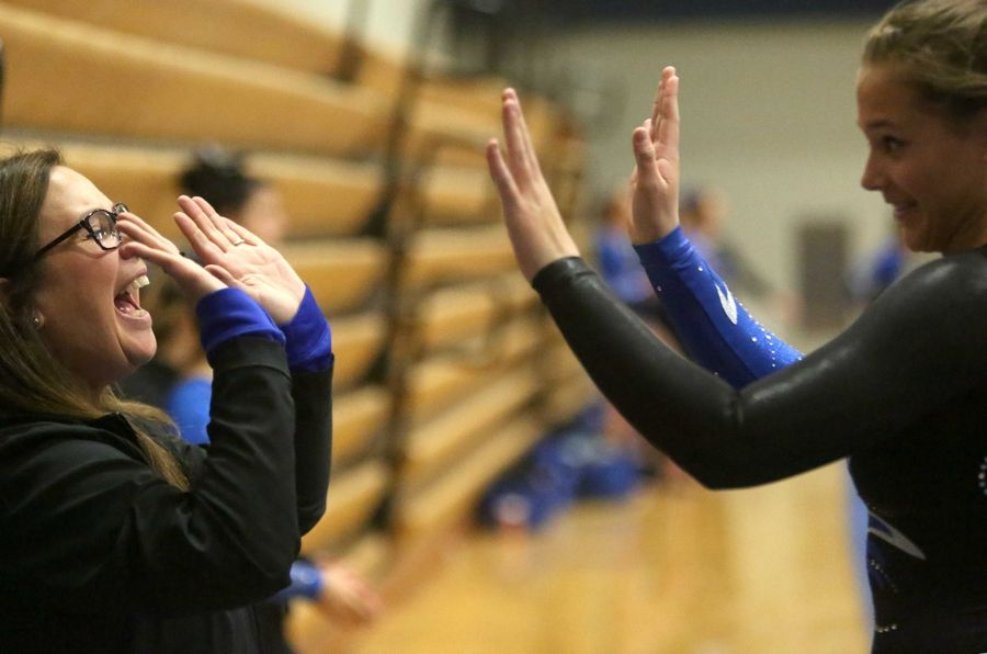Geneva's Gracie DeVita, right, celebrates with head coach Kim Hostman after a vault during varsity gymnastics action at Mack Olson Gym on the campus of Geneva High School Wednesday night.