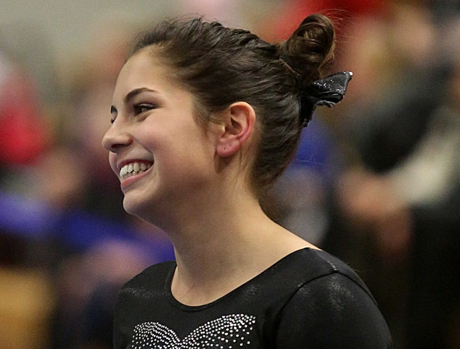 U-46 co-op's Kya Michels smiles before her beam routine during varsity gymnastics action at Mack Olson Gym on the campus of Geneva High School Wednesday night.