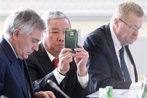 International Olympic Committee, IOC, Vice President Zaiqing Yu, center, from China, looks at his mobile phone next to Vice President John Coates, right, from Australia and IOC Vice President Juan Antonio Samaranch Salisachs, left, from Spain at the opening of the first day of the executive board meeting of the IOC in Lausanne, Switzerland, Tuesday, Dec. 6, 2016. (Laurent Gillieron/Keystone via AP)