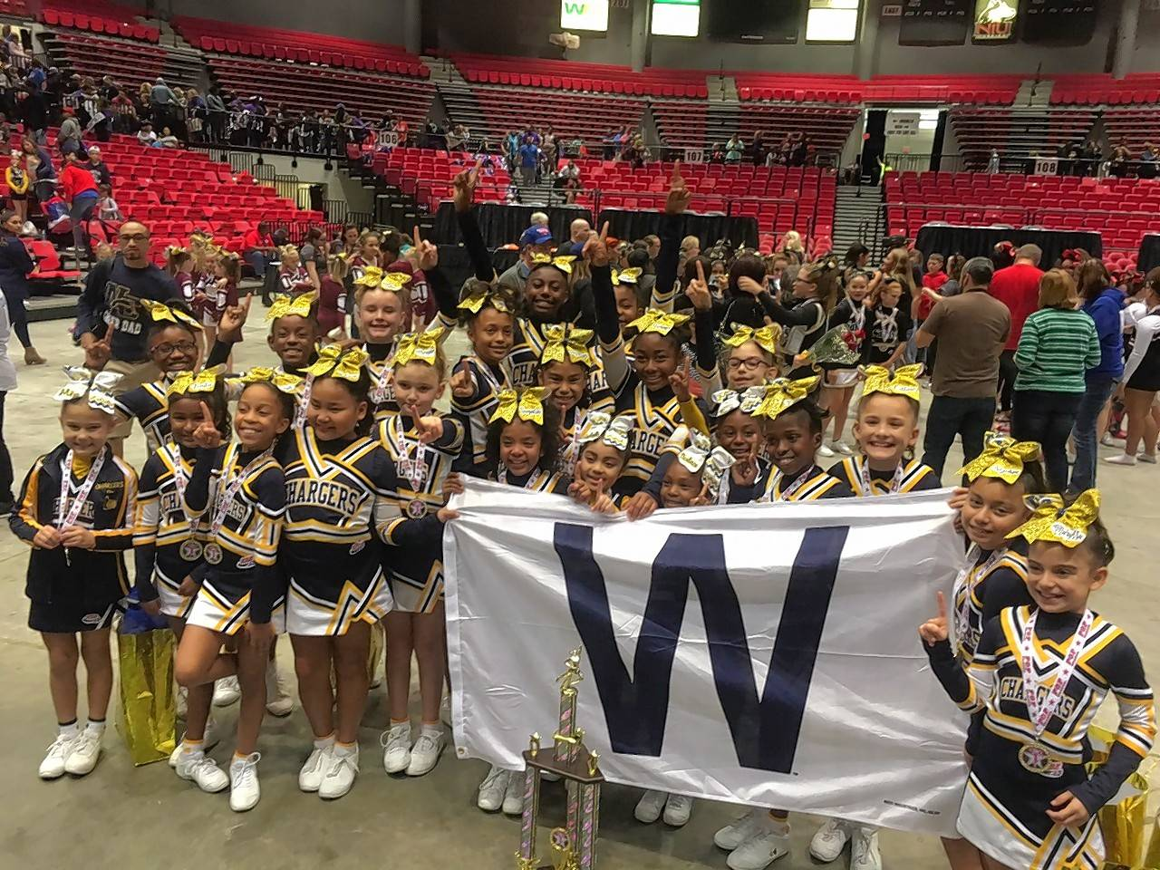 Members of the Naperville Chargers cheerleading teams at the Tiny Mite level for ages 5 to 7 and the Junior Pee Wee level for ages 8 to 11 celebrate the Regional championship victory of the older team during a competition Nov. 6 at Northern Illinois University. The Junior Pee Wee team is competing this week in the Pop Warner Cheer and Dance National Championships in Florida.