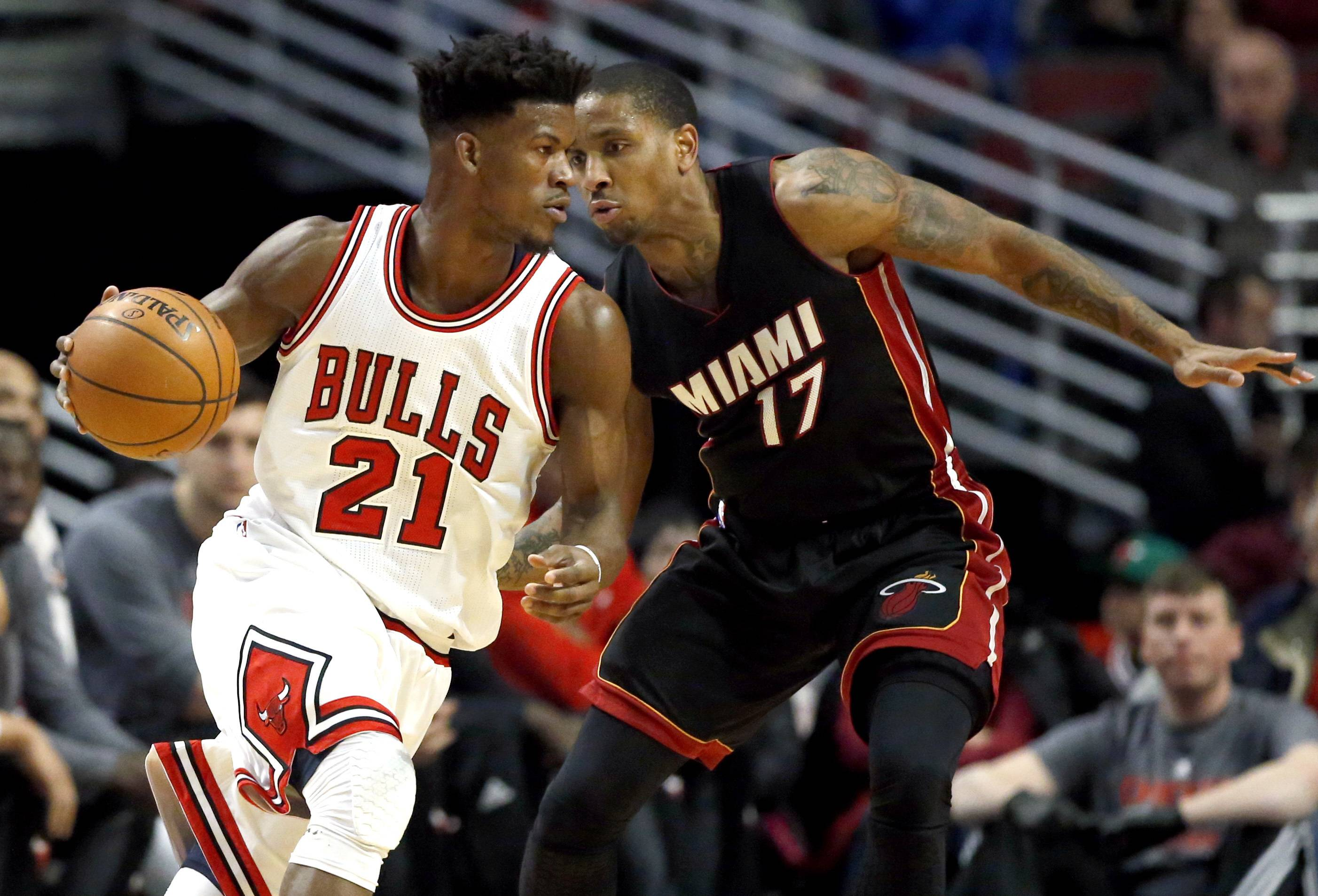 Chicago Bulls guard/forward Jimmy Butler, left, drives against Miami Heat guard Rodney McGruder during the first half of an NBA basketball game Saturday, Dec. 10, 2016, in Chicago. (AP Photo/Nam Y. Huh)