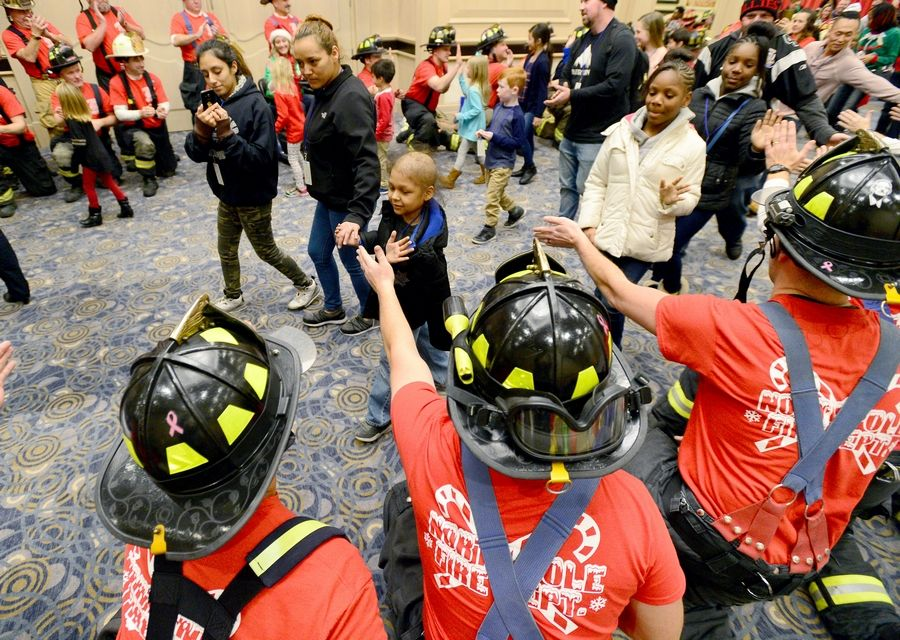 Firefighters reach out to welcome guests to the Operation North Pole Christmas Party for seriously ill children and their families Saturday at the Donald E. Stephens Convention Center in Rosemont.