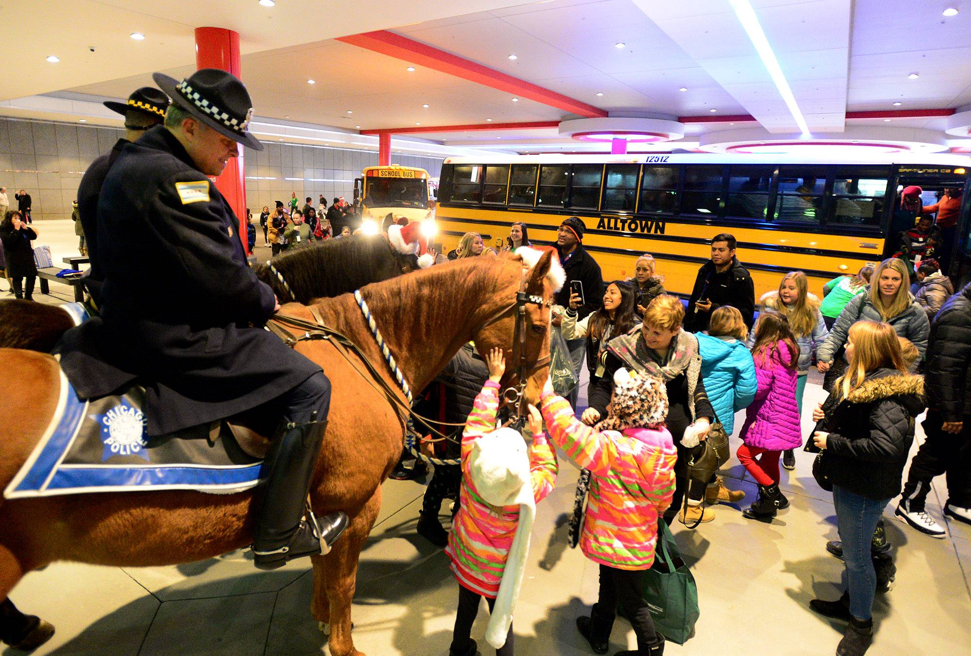 Chicago Police Mounted Patrol officer Richard Jalloway, sitting on Mahoney, greets families at the annual Operation North Pole Christmas Party for seriously ill children and their families Saturday at the Donald E. Stephens Convention Center in Rosemont.
