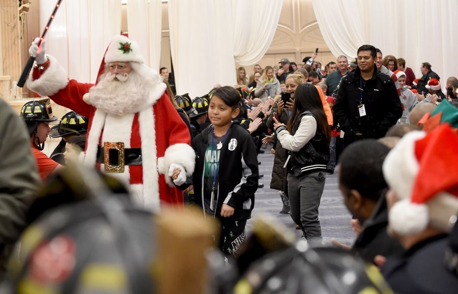 Santa leads a parade of guests at the annual Operation North Pole Christmas Party through a gauntlet of cheering police officers and firefighters. The party for seriously ill children and their families was Saturday at the Donald E. Stephens Convention Center in Rosemont.