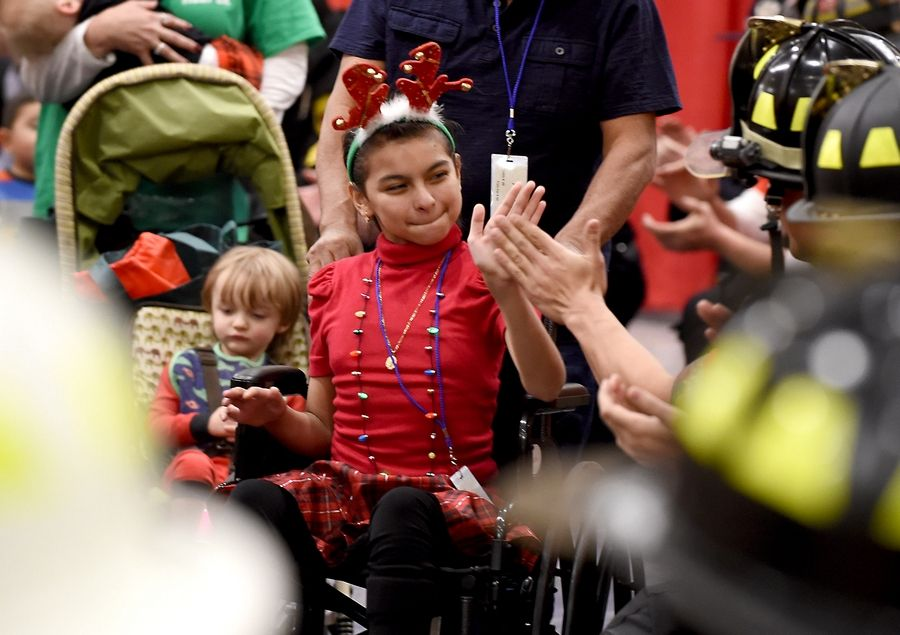 Miranda Cervantes 9, of Cicero gives high-fives as she gets pushed in a wheelchair through the gauntlet of public service officers. Firefighters and police officers from the West and Northwest suburbs threw their annual Operation North Pole Christmas Party for seriously ill children and their families Saturday at the Donald E. Stephens Convention Center in Rosemont.