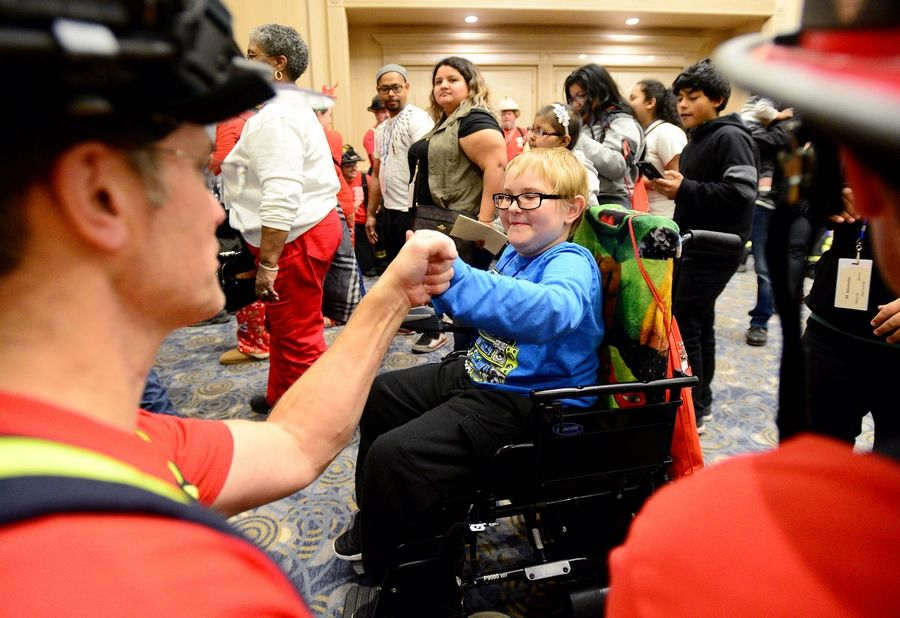 Johnathan Suerth, 10 of Cary, gets a fist bump from Lake Zurich firefighter/paramedic Greg Brendle. Firefighters and police officers from the West and Northwest suburbs threw their annual Operation North Pole Christmas Party for seriously ill children and their families Saturday at the Donald E. Stephens Convention Center in Rosemont.