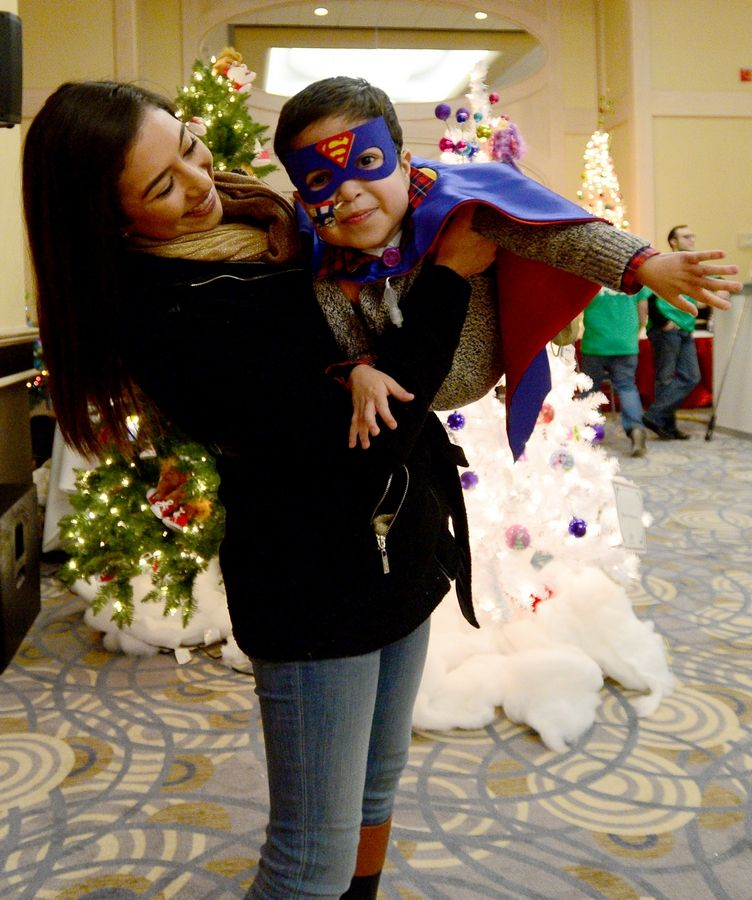 Wearing a superman mask and cape, Michael Caballero, 4, of Aurora flies through the air with help from his big sister Janette Mendoza. Firefighters and police officers from the West and Northwest suburbs threw their annual Operation North Pole Christmas Party for seriously ill children and their families Saturday at the Donald E. Stephens Convention Center in Rosemont.