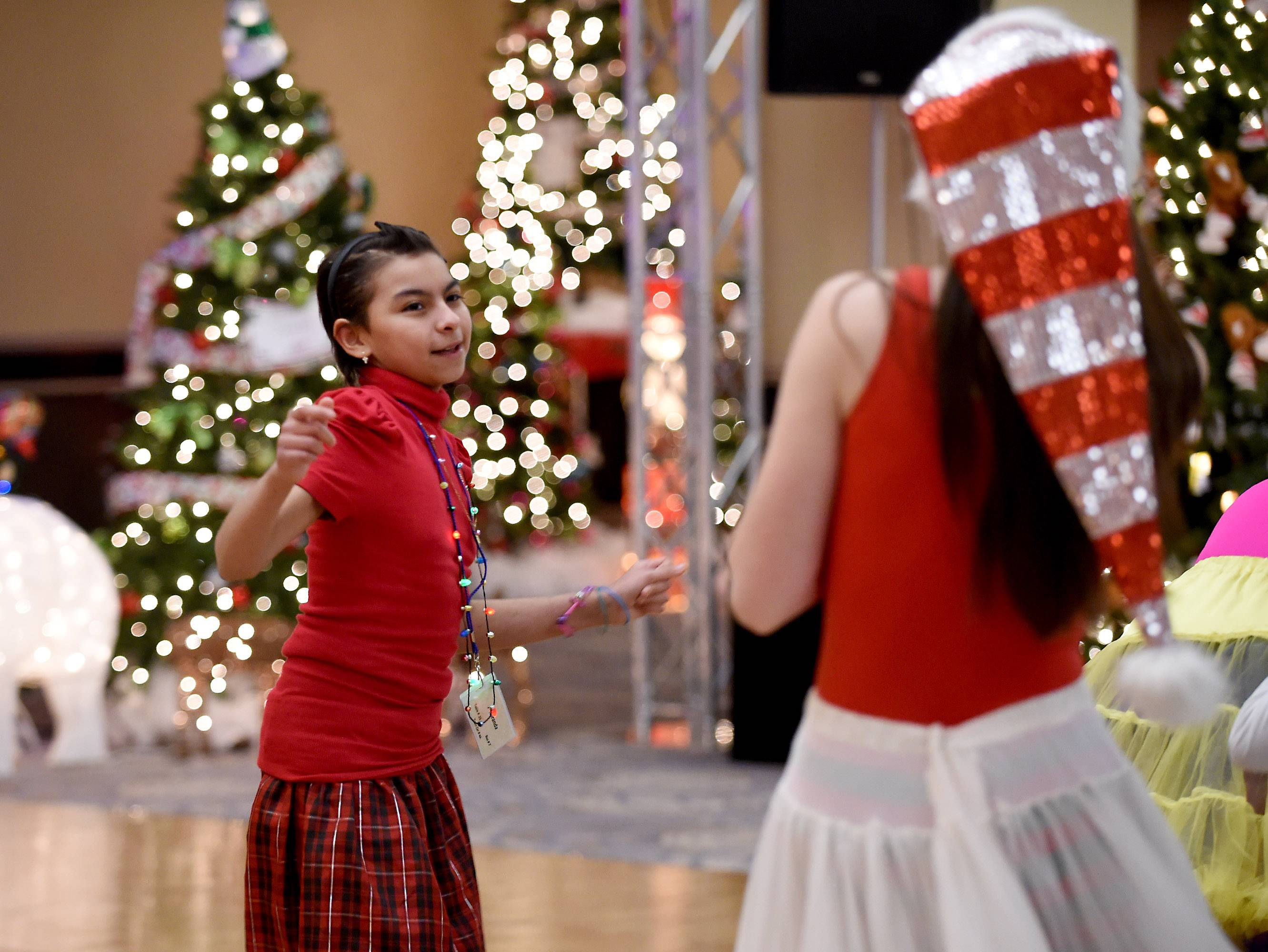 Miranda Cervantes 9, of Cicero, gets out of her wheelchair to dance at the annual Operation North Pole Christmas Party for seriously ill children and their families Saturday at the Donald E. Stephens Convention Center in Rosemont.