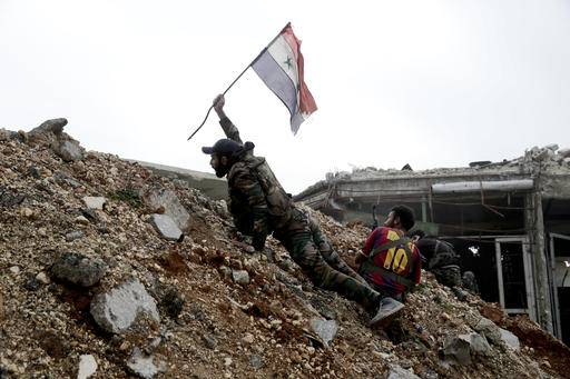 FILE - In this Monday, Dec. 5, 2016 file photo, a Syrian army soldier places a Syrian national flag during a battle with rebel fighters at the Ramouseh front line, east of Aleppo, Syria. Aleppo is set to be recaptured by Syrian President Bashar Assad, but the victory will not be Assad's alone. The battle for Syria's largest city has attracted thousands of foreign forces, including Russian soldiers and thousands of fighters from Iran, Lebanon, Iraq and Afghanistan. (AP Photo/Hassan Ammar, File)