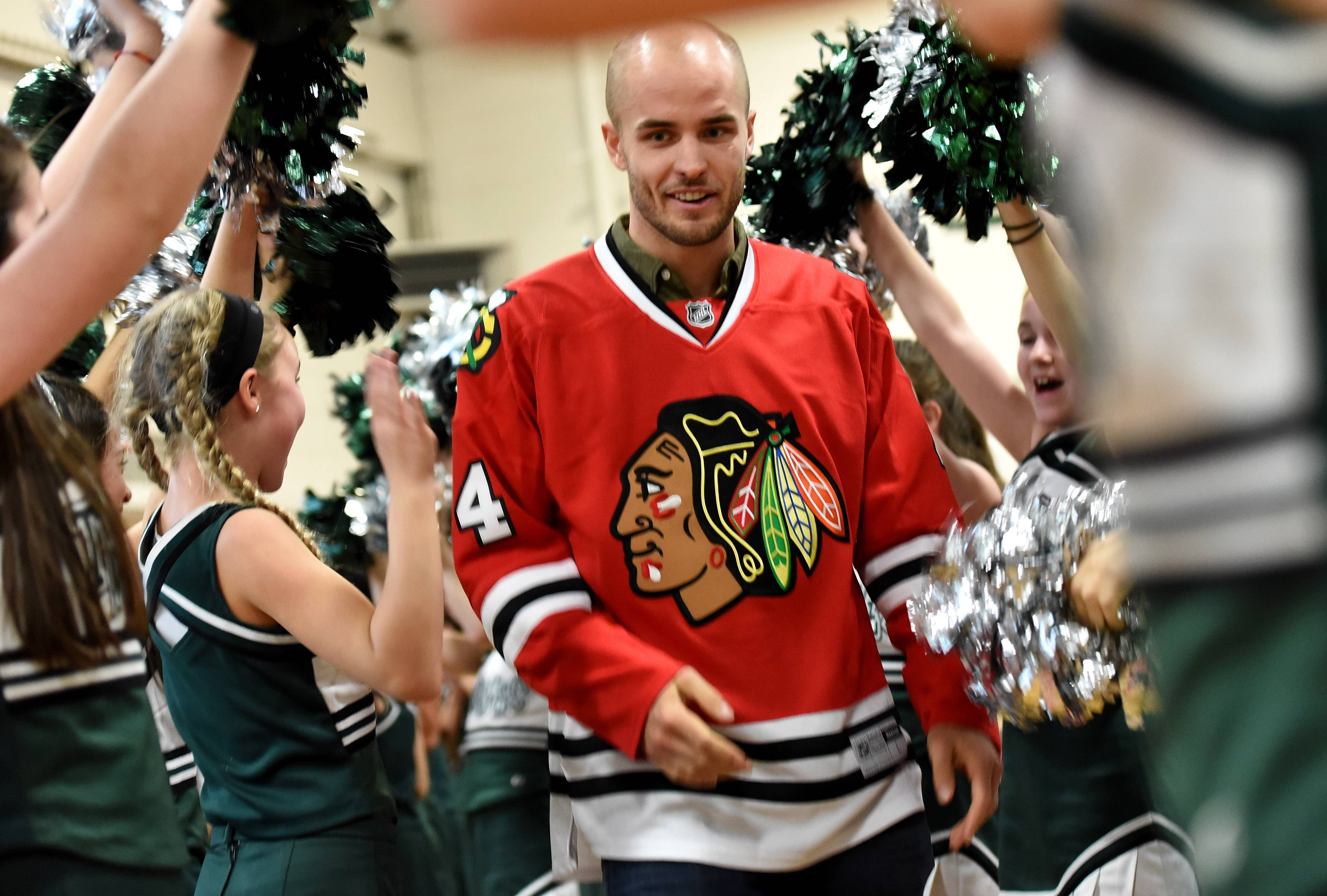 Chicago Blackhawks defenseman Niklas Hjalmarsson runs the gauntlet of cheerleaders and pom pon girls during his vistit to Thomas Middle Schoolin Arlington Heights. His visit was to help recognize the school's efforts in the Pass it On Donation Challenge.