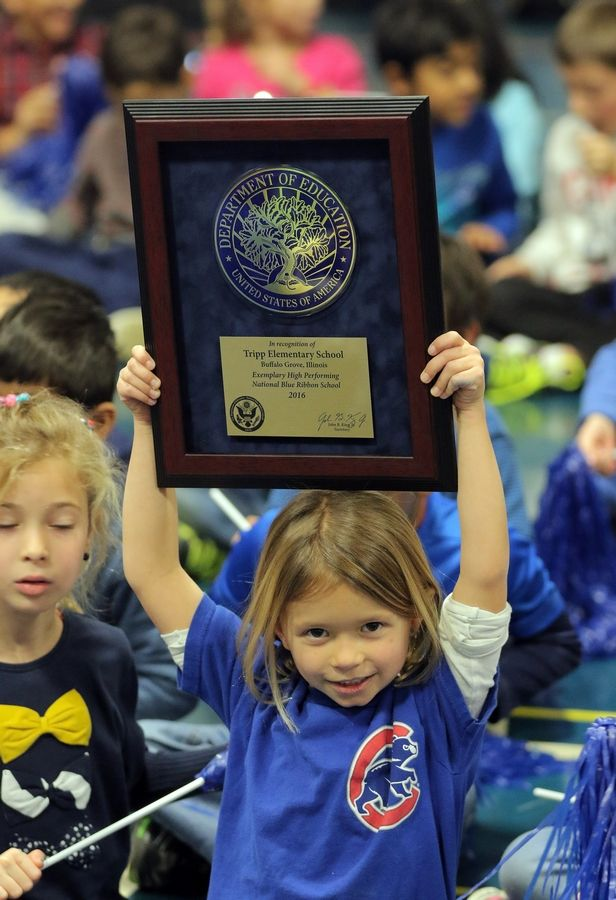 Tripp Elementary School first grader Addison Libbey holds the 2016 U.S. Department of Education National Blue Ribbon School award during an celebration assembly Monday in Buffalo Grove.