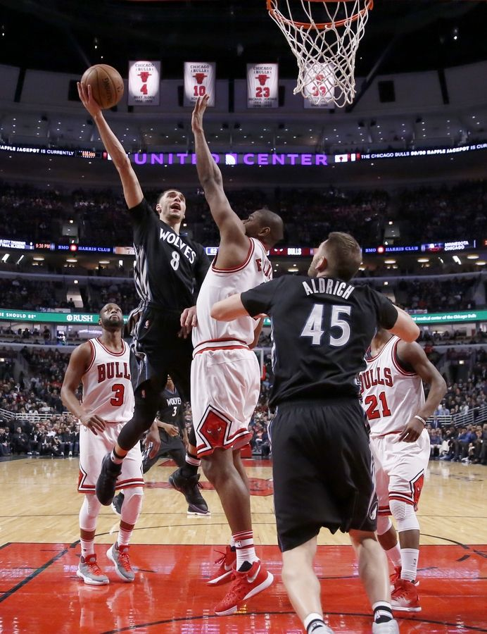 Minnesota's Zach LaVine (8) scores over Bulls center Cristiano Felicio, as Dwyane Wade, Jimmy Butler, and Cole Aldrich (45) watch. The Timberwolves won 99-94 Tuesday, with LaVine netting 24 points, 6 rebounds and 6 assists.