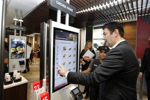 FILE - In this Thursday, Nov. 17, 2016, file photo, McDonald's CEO Steve Easterbrook demonstrates an order kiosk, with cashier Esmirna DeLeon, during a presentation at a McDonald's restaurant in New York's Tribeca neighborhood. Restaurant chains including McDonald's and Olive Garden are rolling out options like ordering kiosks and tabletop tablets. Those changes may eventually reduce or change the nature of restaurant jobs, but stem more from the industry adapting to customer habits, and are likely regardless of wages.