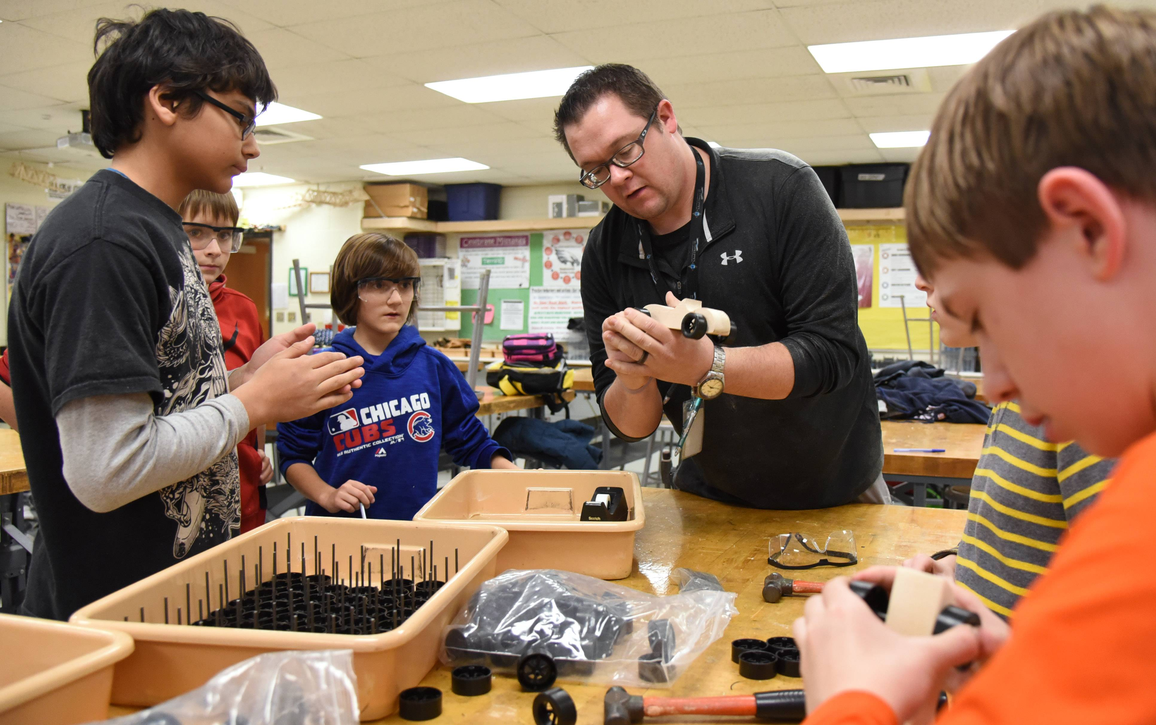 Lake Zurich Middle School South applied technology teacher Eric Prostka directs woodworking club students as they make toy cars presented Wednesday to the Caring Women's Connection of Hawthorn Woods. The toys will be given to children in need.