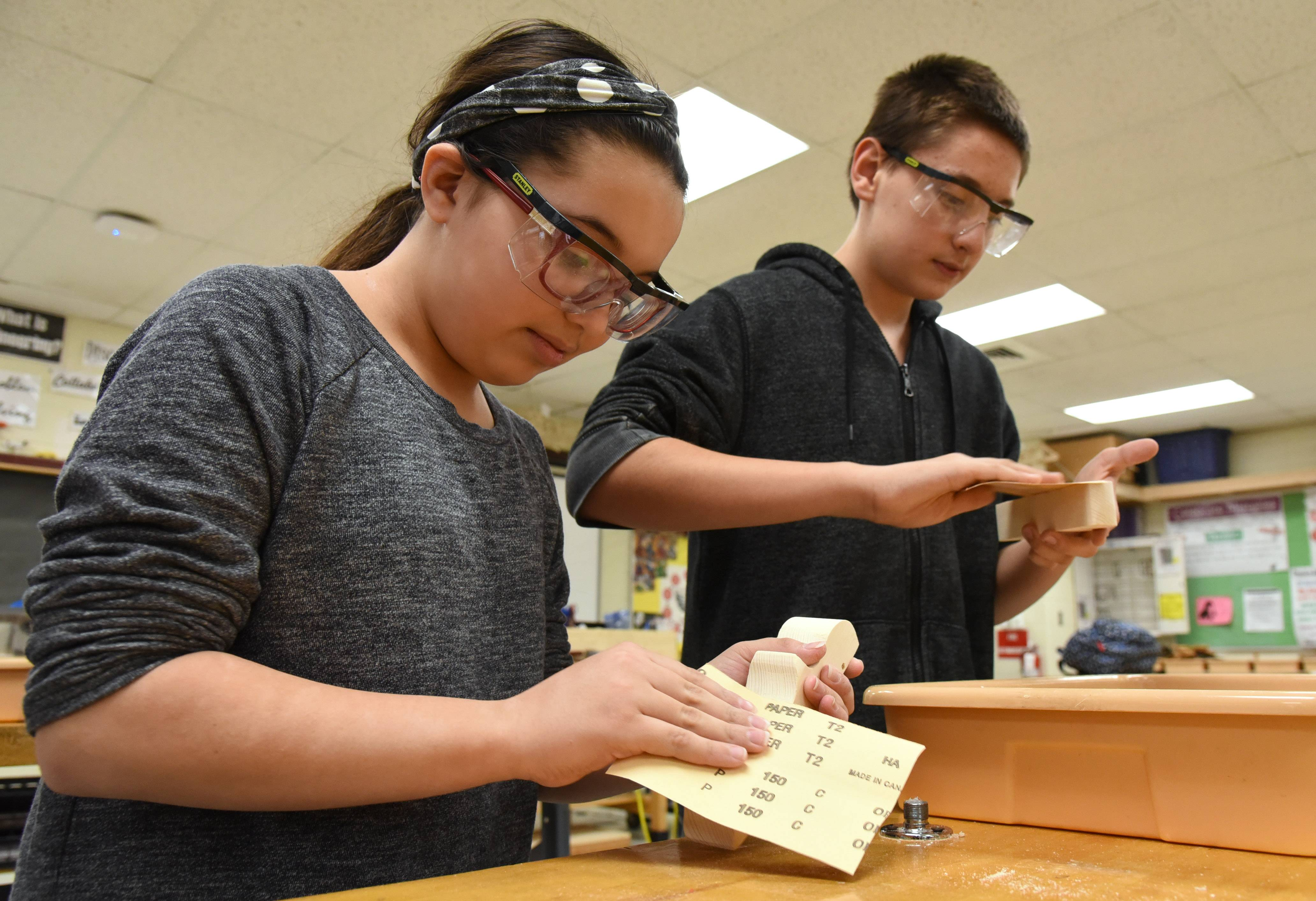 Lake Zurich Middle School South woodworking club members Izzy Ahumada, left, and Jacob Belovicz, both seventh-graders, make toy cars that will be given to children in need.