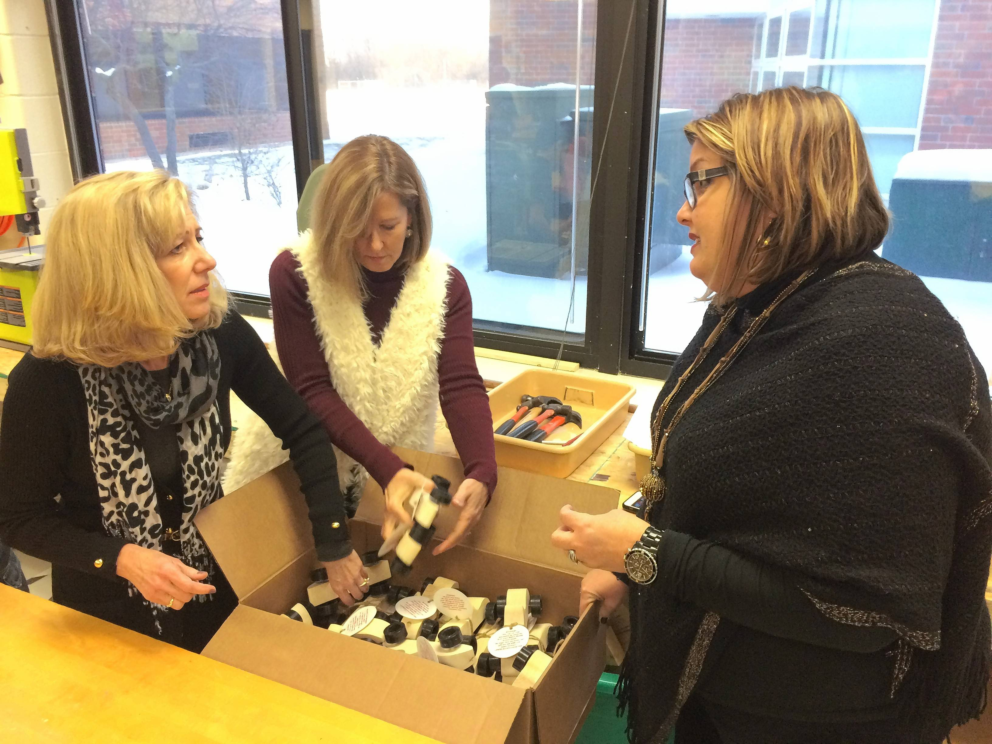 From left, Susan Passaglia, Chris Geimer and Laurie Wilhoit of Caring Women's Connection of Hawthorn Woods on Wednesday accepted 100 toy cars built by Lake Zurich Middle School South woodworking club members.