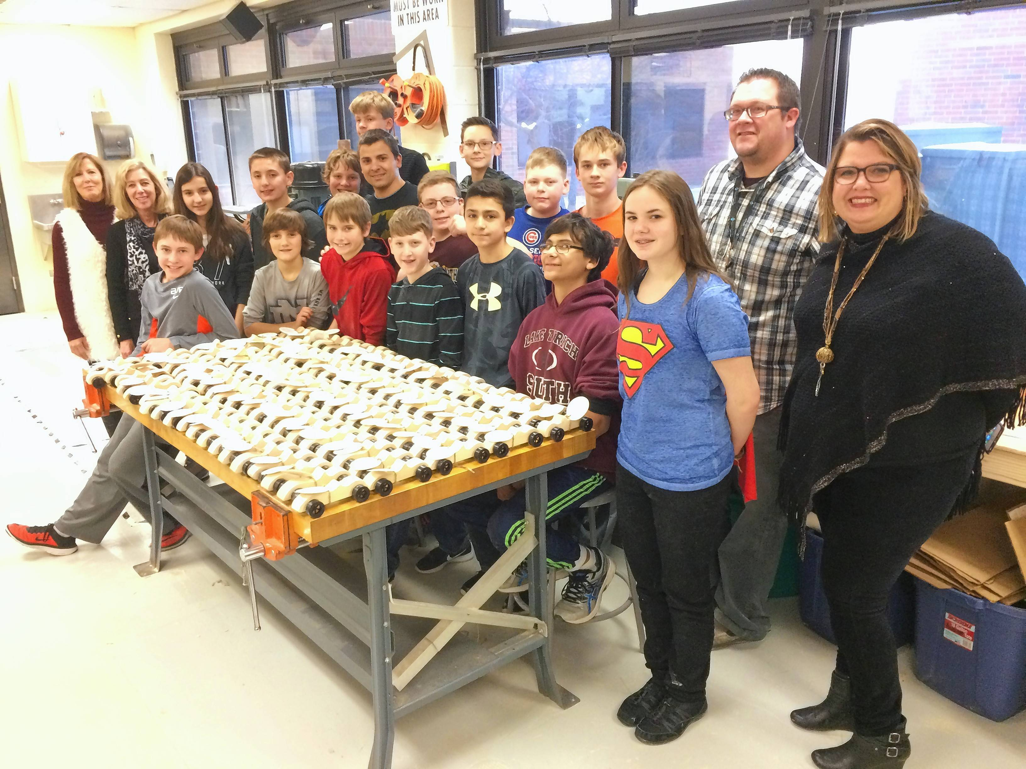Members of Caring Women's Connection of Hawthorn Woods and Lake Zurich Middle School South woodworking club members gather Wednesday for a group shot after the students presented 100 toy cars to the nonprofit organization to donate to less fortunate children.