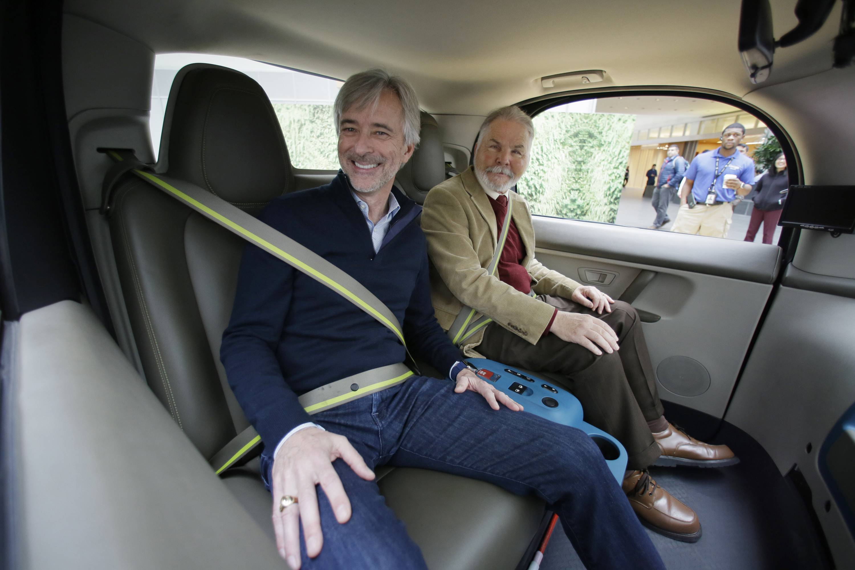 Waymo CEO John Krafcik, left, sits with Steve Mahan, who is blind, inside a driverless car during a Google event, Tuesday, Dec. 13, 2016, in San Francisco. In 2015, Mahan became the first member of the public to ride in Google's self-driving prototype, alone and on public roads.