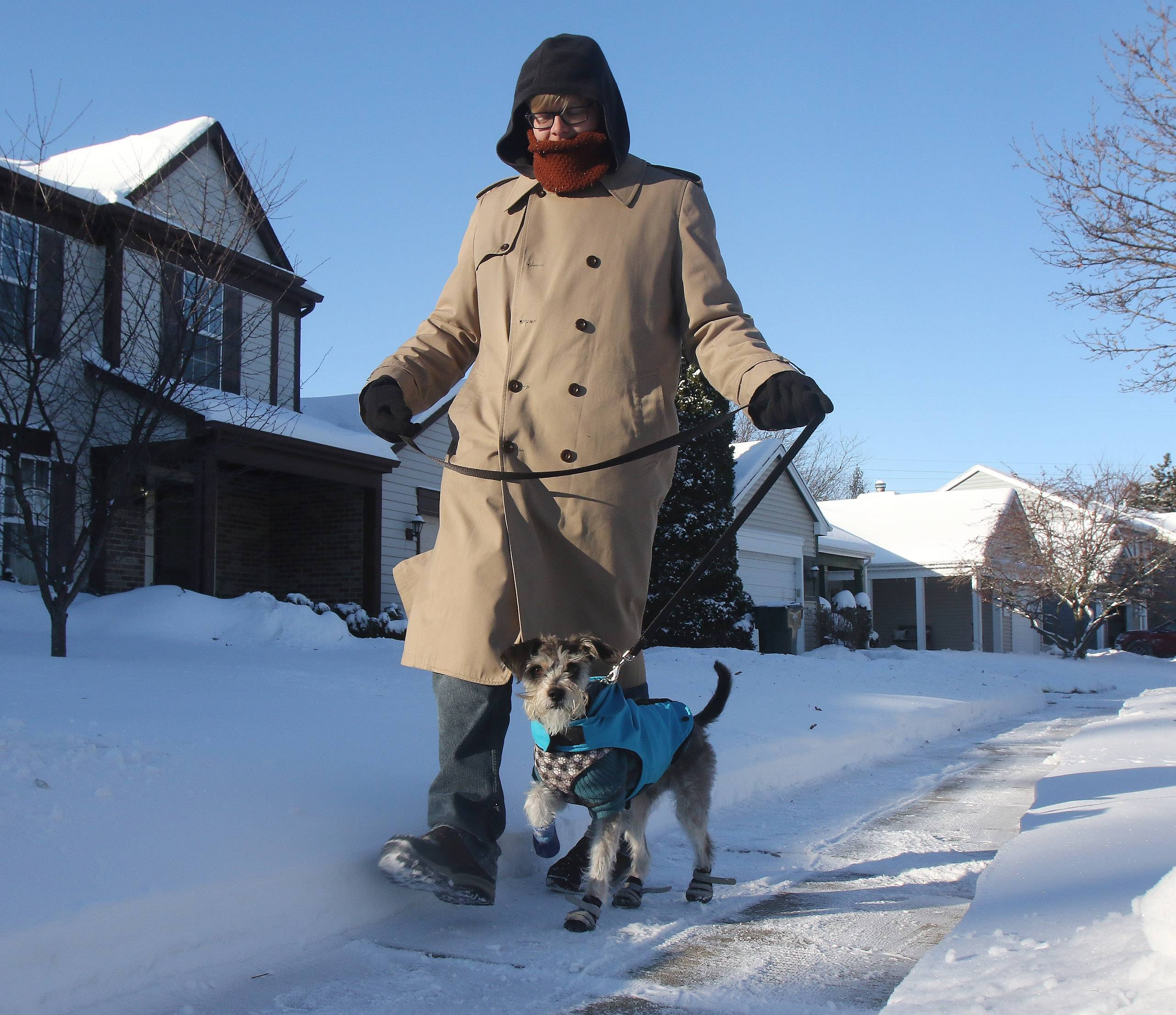 "Anthony Fiorelli walks with his dog, Hamilton, in Mundelein on Sunday as people woke up to frigid temperatures in the suburbs. ""I don't mind the snow myself but I can't deal with this 2, 3, 4 degrees nonsense,"" said Fiorelli as he bundled up for the cold and put bootees on his dog."