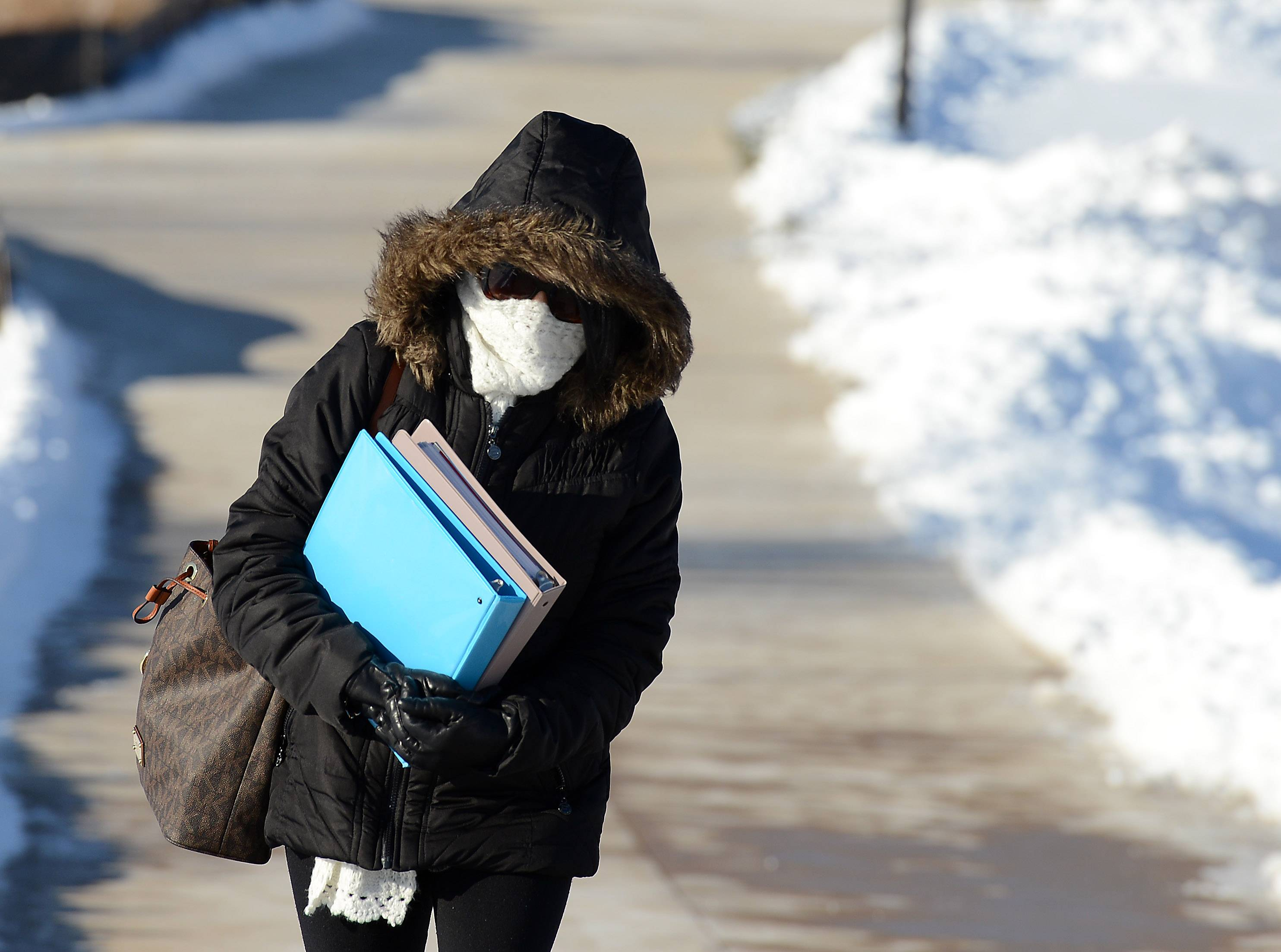 With a windchill temperature at -10 degrees, Maria Becker of Bartlett keeps as little of her skin showing as possible as she walks to her car at Elgin Community College Thursday.
