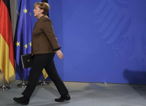 German Chancellor Angela Merkel leaves after a statement at the chancellery  in Berlin, Friday,