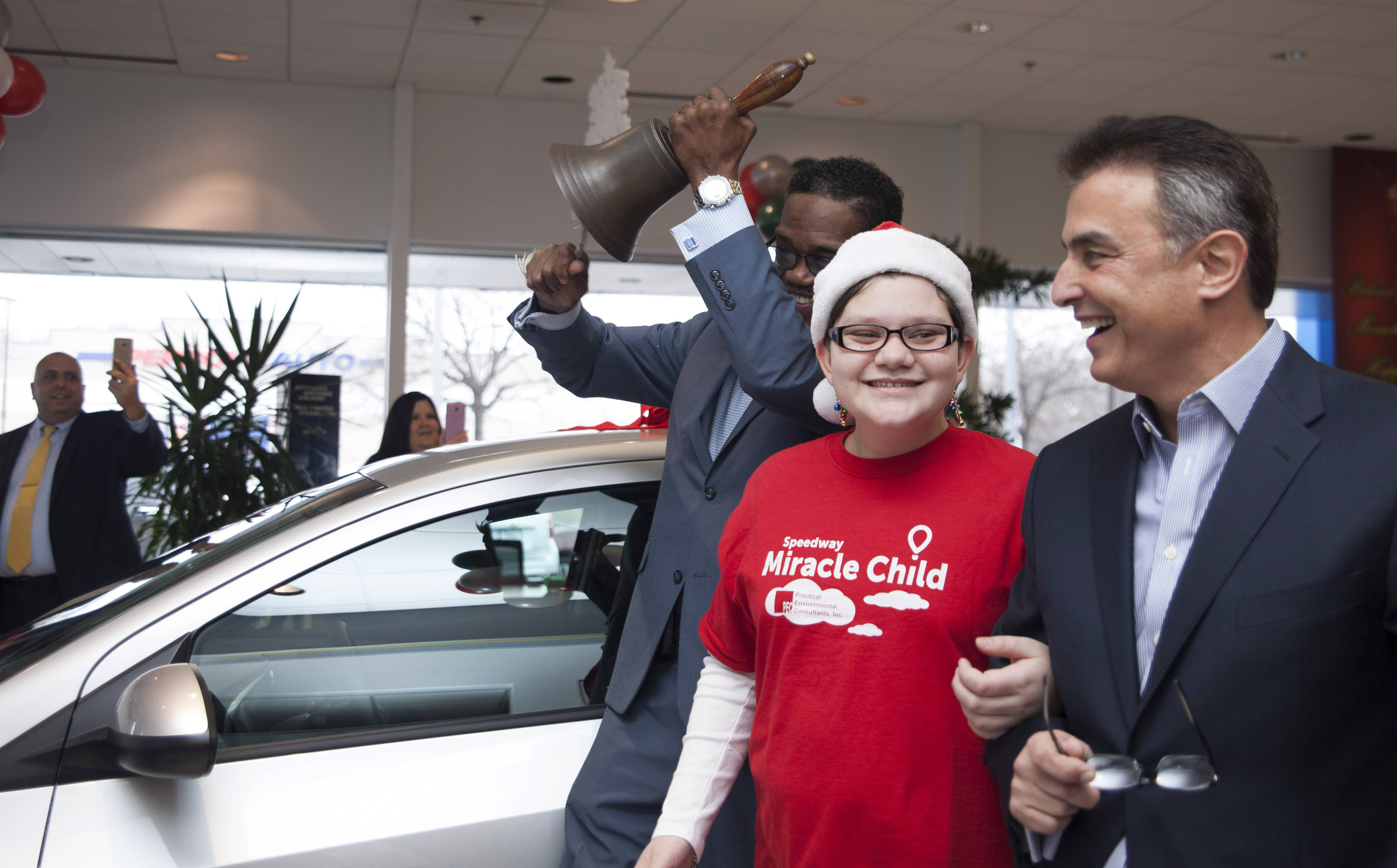 Rosie Colucci of Palatine is all smiles Saturday as her family receives the new car. Rosie is escorted by Chevrolet of Homewood owner Steve Phillipos, right.