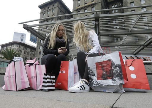 FILE - In this Nov. 25, 2016, file photo, Maddy, left, and her friend Maggie, sit with their shopping bags at Union Square in San Francisco. The holiday shopping season is losing some of its power in the year's sales. November and December now account for less than 21 percent of annual retail sales at physical stores, down from a peak of over 25 percent. The shift is in part because people are spreading out their shopping all year, demanding big discounts and spending more on events rather than more stuff.