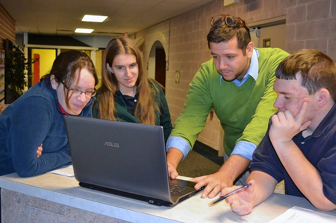 Former Naperville Christian Academy students Alex Veague, a 2014 graduate; Kaitlyn MacIntyre, a 2013 graduate; and Stevie Melter, right, the other 2013 graduate, work with science teacher Josh Jacobs, center, during their time at the small, private school.