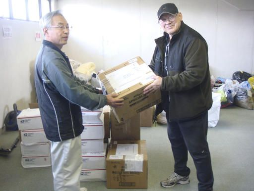 "In this photo provided by Joseph Roginski, taken May 13, 2011, Joseph Roginski, right, holds a package in a storeroom of the Misawa City Hall in Japan, where donations of clothing and supplies were being kept for earthquake relief efforts. He says that while the cost of living is higher in Japan, access to health care is not. ""Things are very expensive here. It is impossible to live off Social Security alone,� said Roginski, who was stationed in Japan in 1968. ""But health insurance is a major factor in staying here.� The former military language and intelligence specialist said he pays $350 annually to be part of Japan's national health insurance. His policy covers 70 percent of his costs. The rest is covered by a secondary insurance program for retired military personnel. (Joseph Roginski via AP)"