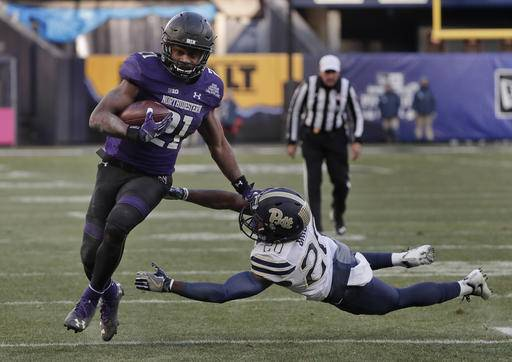 Northwestern running back Justin Jackson (21) runs the ball for a touchdown as he avoids a tackle by Pittsburgh defensive back Dennis Briggs (20) during the second quarter of the Pinstripe Bowl NCAA college football game, Wednesday, Dec. 28, 2016, in New York.