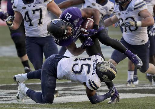 Northwestern running back Justin Jackson (21) is hit by Pittsburgh defensive back Reggie Mitchell (15) during the first quarter of the Pinstripe Bowl NCAA college football game, Wednesday, Dec. 28, 2016, in New York.