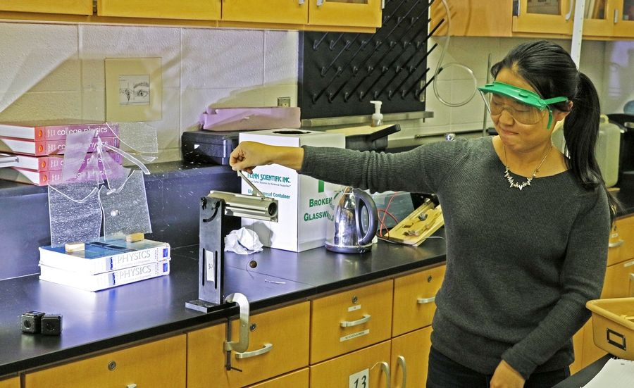 Stacey Ni uses a projectile launcher which shoots a ball bearing and is recorded with a 15,000-per-second frame rate camera to be viewed in slow motion. Special science projects are part of Naperville North High School science teacher Mark Rowzee's class.