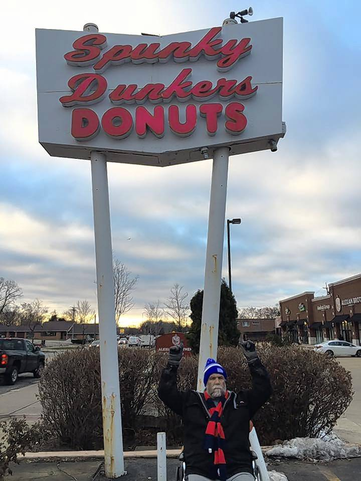 Beloit, Wisconsin, resident Dennis Schulze is traveling down Northwest Highway through the suburbs via wheelchair, hoping to reach Wrigley Field by Friday. Schulze is making the journey to raise money for a number of charities, including the March of Dimes and the Wounded Warrior Project. In this photo, he poses at Spunky Dunkers doughnuts in Palatine.