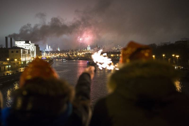 People watch as fireworks explode over the Moscow' Kremlin, and are reflected in the Moscow River during the New Year celebrations in Moscow, Russia, Sunday. New Year's Eve is Russia's major gift-giving holiday, and big Russian cities were awash in festive lights and decorations.