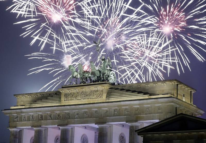 Fireworks light the sky above the Quadriga at the Brandenburg Gate shortly after midnight in Berlin, Germany, Sunday, Jan. 1, 2017. Hundred thousands of people celebrated New Year's Eve welcoming the new year 2017 in Germany's capital.