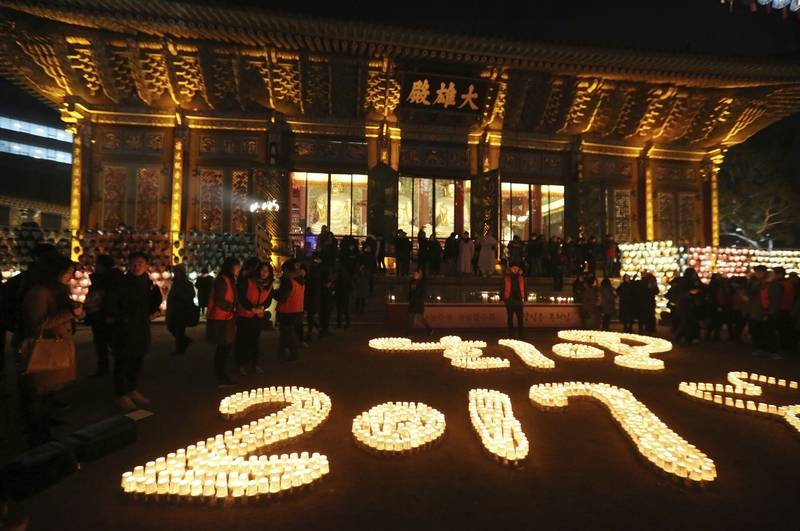 Buddhists light candles during New Year celebrations at Jogye Buddhist temple in Seoul, South Korea, early Sunday, Jan. 1, 2017.