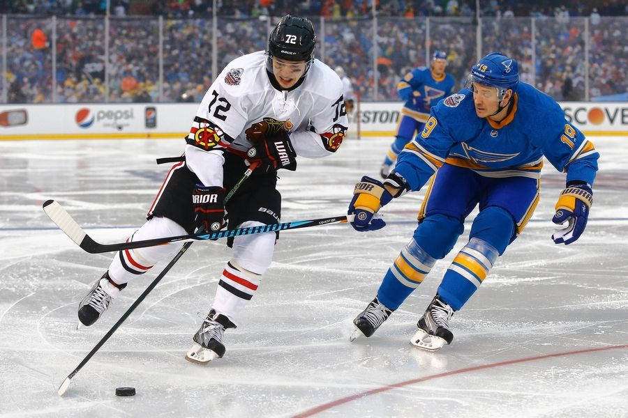 Blackhawks' Artemi Panarin, left, skates with the puck as he is defended by St. Louis Blues' Jay Bouwmeester during the first period of the NHL Winter Classic on Jan. 2 at Busch Stadium in St. Louis.