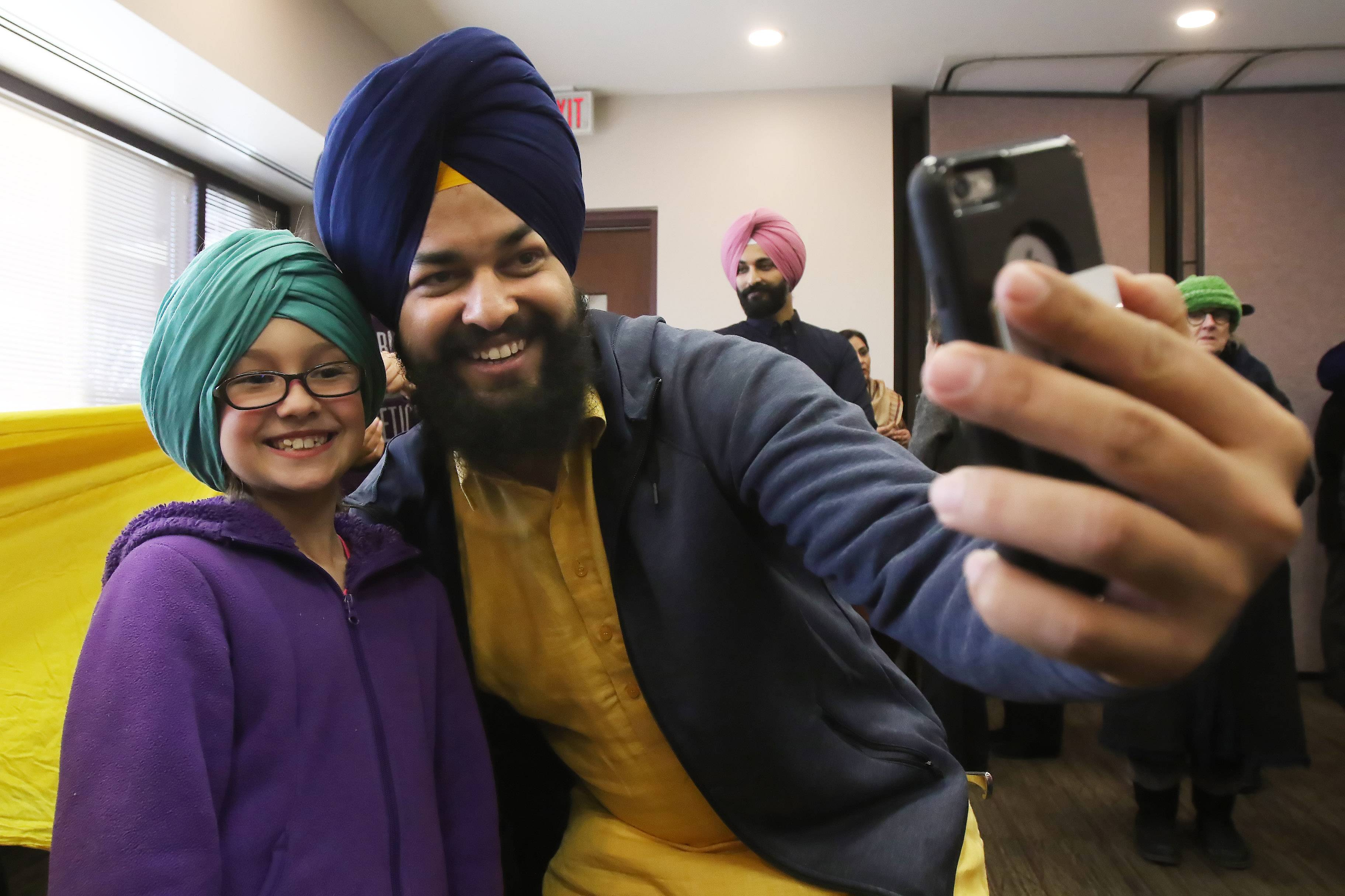 "Gurpreet Singh of Arlington Heights takes a selfie Sunday with 8-year-old Olivia Bertels of Schaumburg after he showed her how to tie a turban on her head during a ""Get to Know Your Sikh Neighbor"" event at the Palatine Public Library."