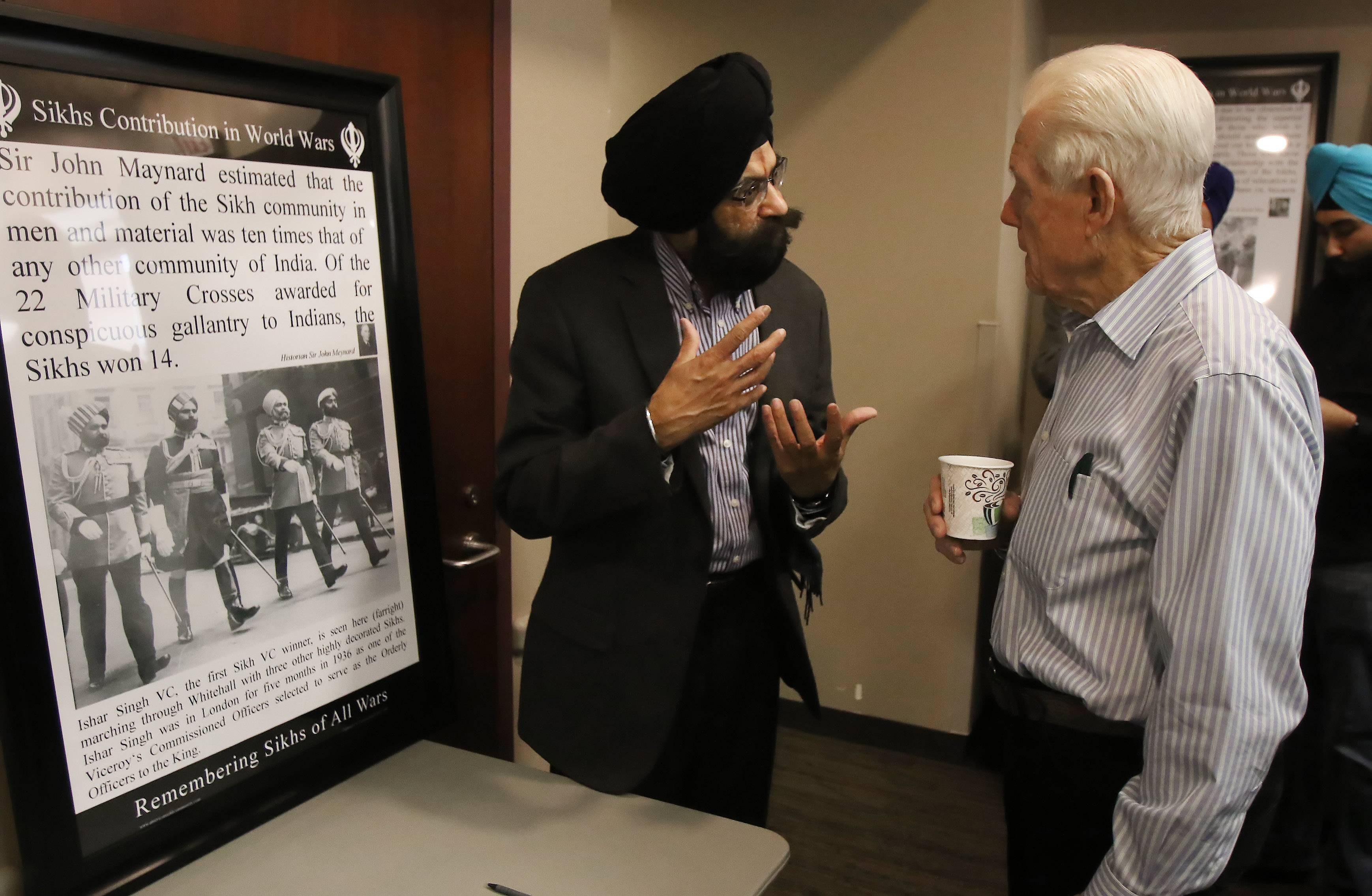 "Sarwan Singh of Schaumburg, left, talks Sunday to Bill Enockson of Barrington about Sikh contributions during both World Wars at ""Get to Know Your Sikh Neighbor"" event at the Palatine Public Library."