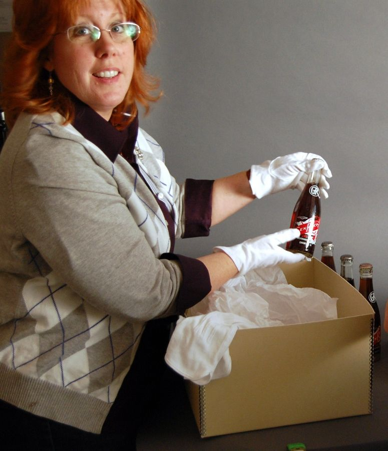 The Lake County Discovery Museum's Diana Dretske holds a Glen Rock soda pop bottle that is part of the museum's collection that will be moved to new quarters in Libertyville.