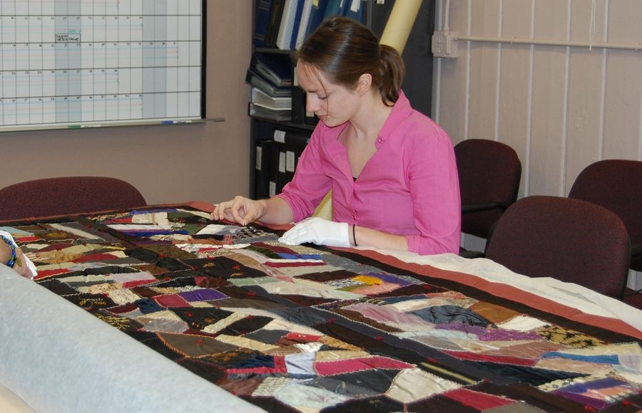The Lake County Discovery Museum's registrar, Corinne Court, works on a quilt. Museum staff are preparing to move the collections to a new location in Libertyville.