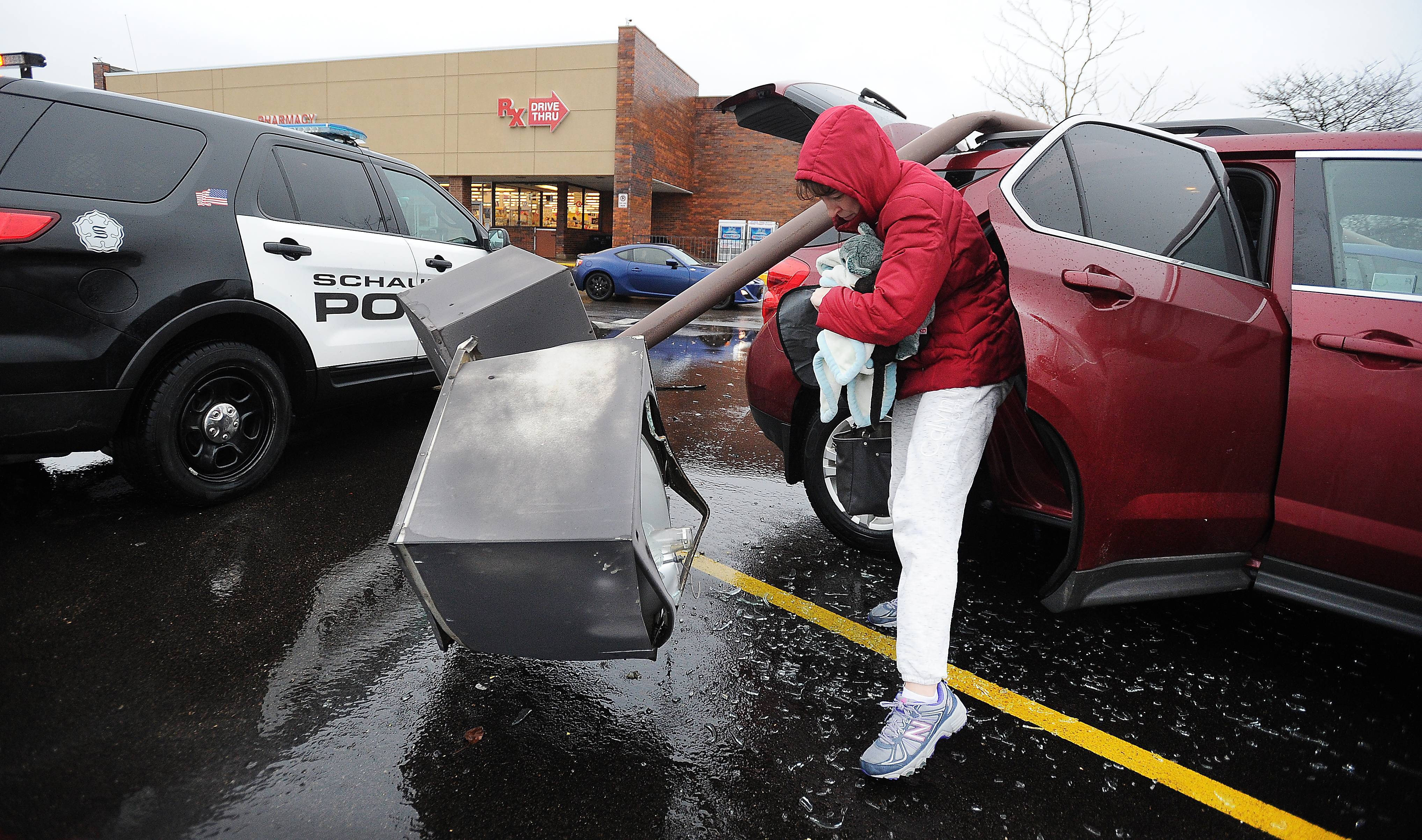 Nicki Scheck of Schaumburg steps gingerly around broken glass Tuesday after high winds toppled a light pole at the Jewel-Osco parking lot at Roselle and Wise roads while she was inside shopping. Her Chevy SUV and a Honda Fit both sustained heavy damage.