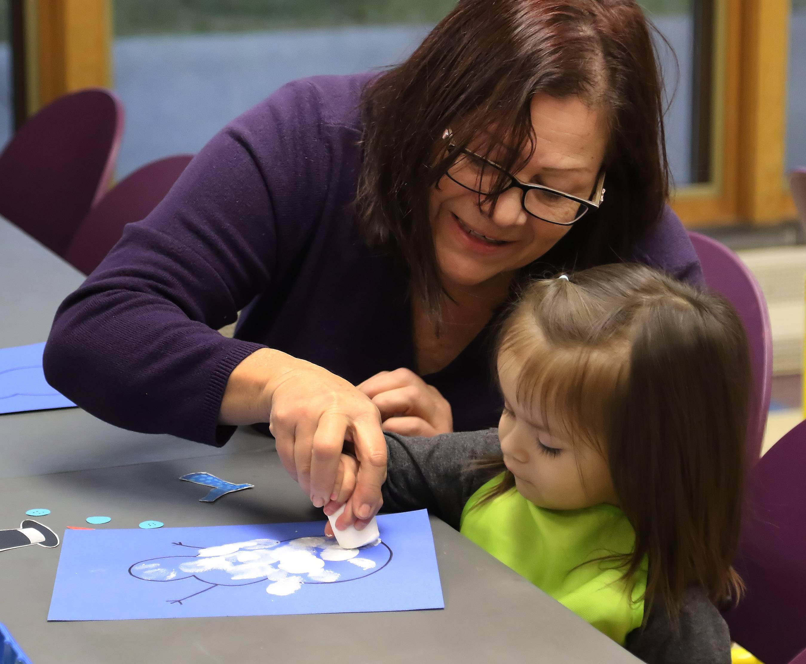 Ida Carillo of Round Lake helps her granddaughter, Isabella Gerrati, 2, use a marshmallow to paint a snowman as toddlers work on snow projects Tuesday during Toddler Art at the Round Lake Area Public Library. The class is held each month for 12- to 24-month-olds to work on hands-on art projects and develop their senses.