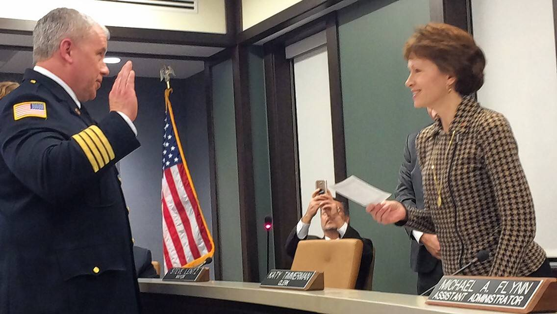 Mundelein's new chief deputy fire chief, William Lark, recites his oath of office Monday with help from Village Clerk Katy Timmerman.